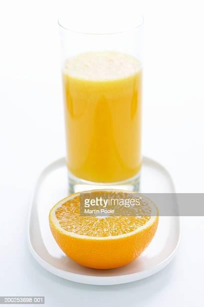 Halved orange by orange juice in glass, close-up