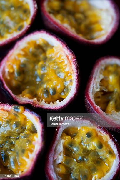 Halved passion fruits showing the insides and skin edges