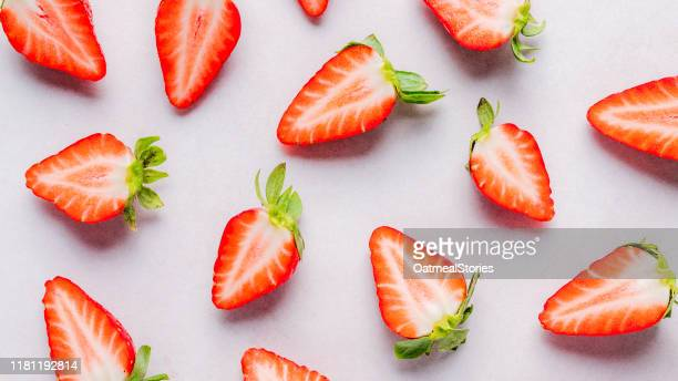 halved strawberries on a pink background - strawberry stock pictures, royalty-free photos & images