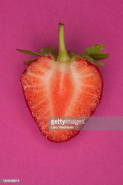 A halved strawberry on a pink background