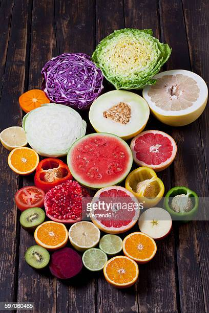 Halves of different vegetables and fruits on dark wood
