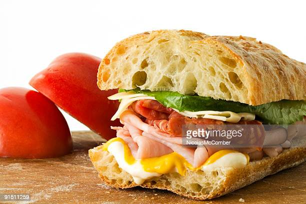 Ham and cheese sandwich in front of tomatoes