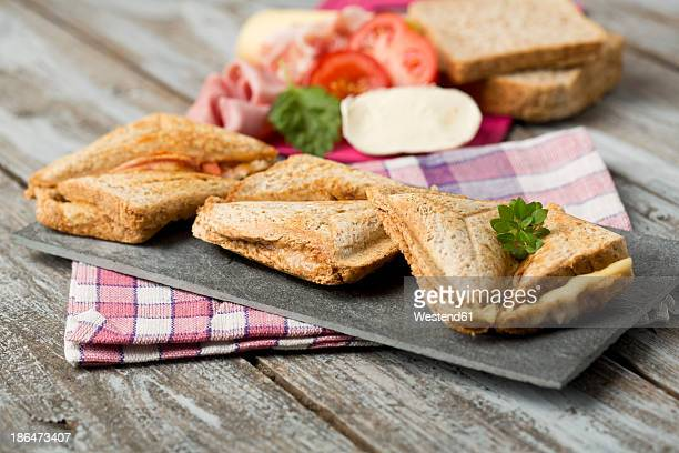Ham and cheese sandwich with tomatoes on chopping board