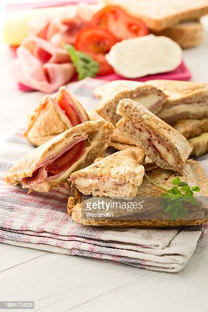 Ham and cheese sandwich with tomatoes on napkin