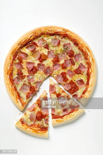 Ham, cheese and tomato pizza (partly sliced)