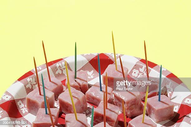 Ham cubes with toothpicks on plate