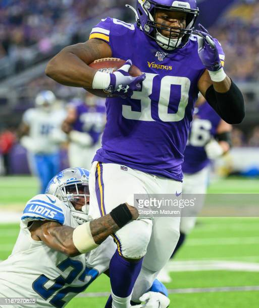 J Ham of the Minnesota Vikings is tackled with the ball by Tavon Wilson of the Detroit Lions in the second quarter of the game at US Bank Stadium on...