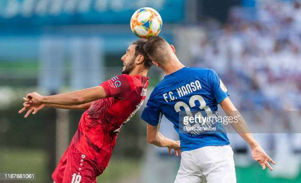 Hamadi Al Ghaddioui of VfB Stuttgart jumps for a header with Sven Sonnenberg of Hansa Rostock during the DFB Cup first round match between Hansa...