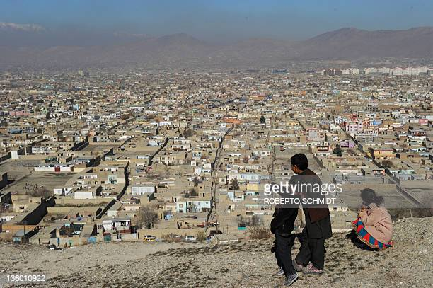 Hamaion points to the city as he his cousin Omid and his sister Frazoun stand on a hilltop park overlooking Kabul on December 16 2011 Hamaion and his...