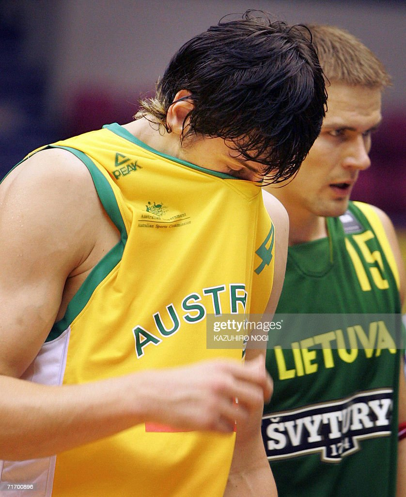 Australian NBA player Andrew Bogut covers his face as he