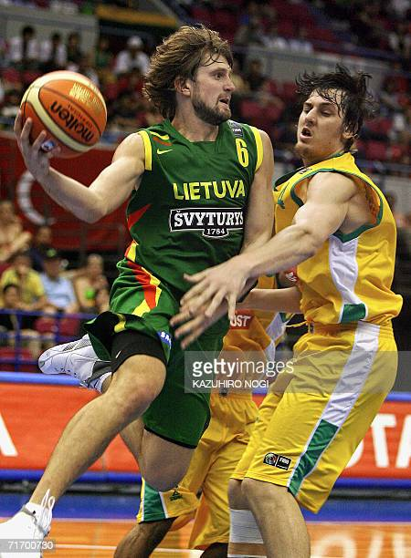 Lithuanian NBA player Arvydas Macijauskas vies with Australian NBA player Andrew Bogut during their Group C preliminary round match on the fifth day...