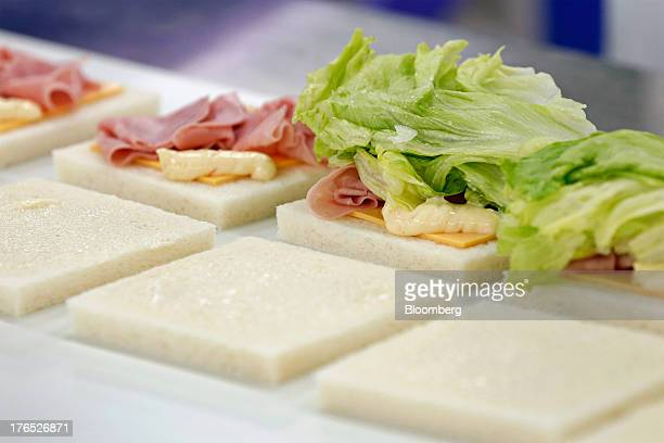 Hamandcheese sandwiches for Seven I Holdings Co's 7Eleven convenience stores move along a conveyor as they are assembled on the production line of...