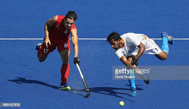Hamanpreet Singh of India plays the ball as Thomas Briels attempts to challenge during the Men's hockey quarter final match between Belgium and India...