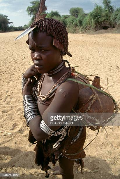 Hamar girl wearing a characteristic ovalshaped metal plate called a kalle which young women wear before marriage Ethiopia