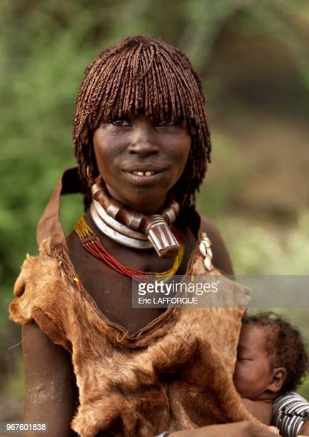 Hamar woman with her baby on October 26 2008 in Omo valley Ethiopia This is a Hamar woman with a one week baby under her goat skin This one is lucky...