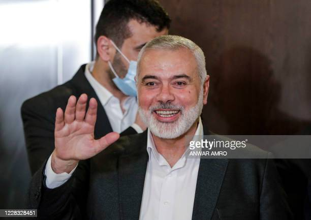 Hamas chief Ismail Haniyeh waves upon arriving for a meeting with representatives of other Palestinian factions at the Palestinian embassy in...