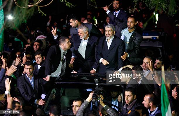 Hamas leader in exile Khaled Meshaal and Gaza's Hamas prime minister Ismail Haniya arrive for a visit to Al-Dallu family, of which 10 members were...