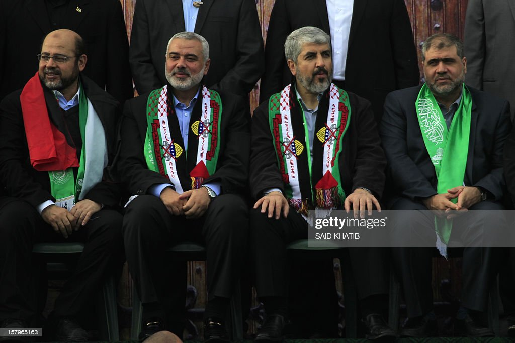 Hamas leader in exile Khaled Meshaal (2nd R) and Hamas prime minister in the Gaza Strip Ismail Haniya (2nd L) attend a rally to mark the 25th anniversary of the founding of the Islamist movement, in Gaza City on December 8, 2012. Meshaal made his first visit to Gaza, timed to coincide with the 25th anniversary of the Islamist movement's founding.