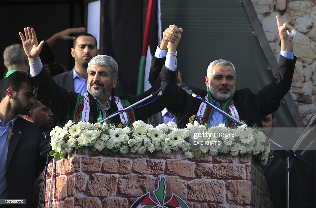 Hamas leader in exile Khaled Meshaal (L) and Hamas prime minister in the Gaza Strip Ismail Haniya (R) gesture to the supporters during a rally to mark the 25th anniversary of the founding of the Islamist movement, in Gaza City on December 8, 2012. Meshaal made his first visit to Gaza, timed to coincide with the 25th anniversary of the Islamist movement's founding.