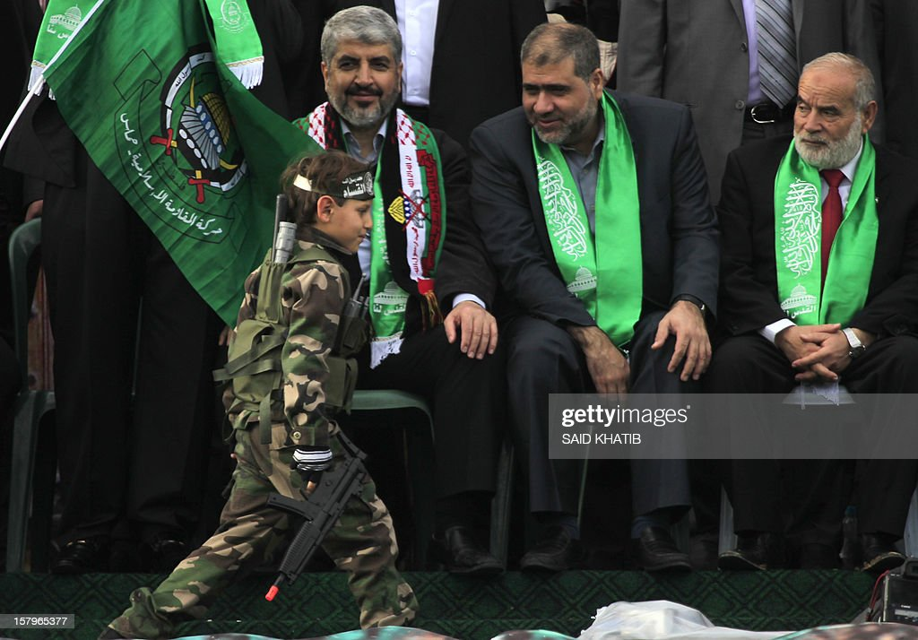 Hamas leader in exile Khaled Meshaal (L) watches a boy dressed in army fatigue walks past during a rally to mark the 25th anniversary of the founding of the Islamist movement, in Gaza City on December 8, 2012. Meshaal made his first visit to Gaza, timed to coincide with the 25th anniversary of the Islamist movement's founding.