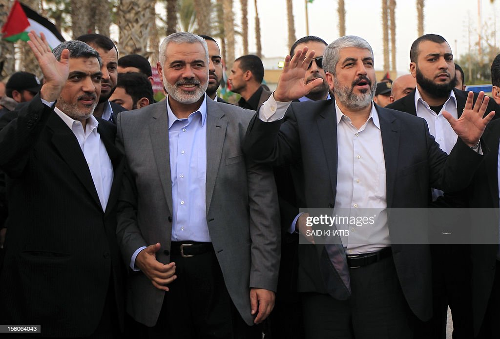 Hamas leader in exile Khaled Meshaal (R) waves goodbye while standing next to Hamas prime minister in the Gaza Strip Ismail Haniya (C) and Hamas leader Izzat al-Rishq (L), upon his departure from the Gaza Strip on December 10, 2012 in Rafah, on the border with Egypt. Exiled Hamas chief Khaled Meshaal left Gaza after a historic first visit to the tiny Palestinian enclave.