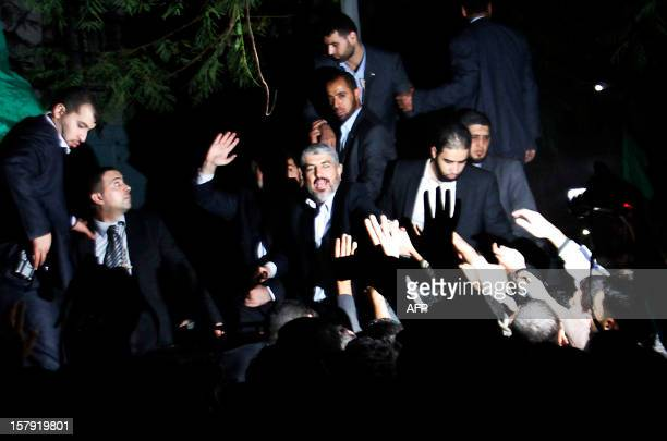 Hamas leader in exile Khaled Meshaal waves to the crowd during a visit to Al-Dallu family, of which 10 members were killed in an Isareli air strike...