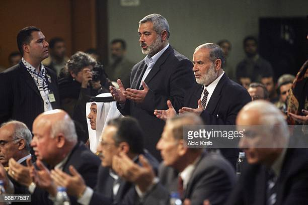 Hamas leaders Ismail Haniyeh and Ahmed Bahar stand as they read a part of the holy Quran during the inaugural parliament session on February 2006 in...
