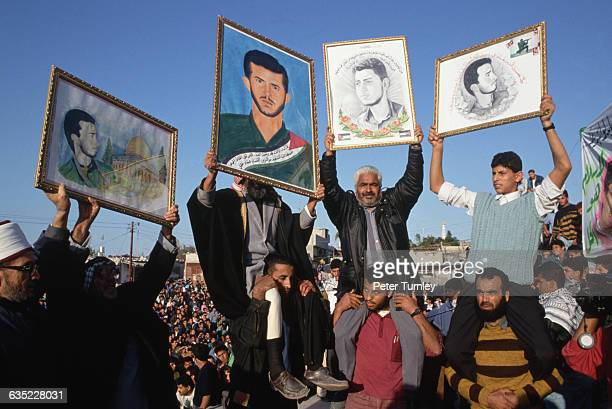 Hamas members hold aloft pictures of a martyred Hamas member at a demonstration in his honor