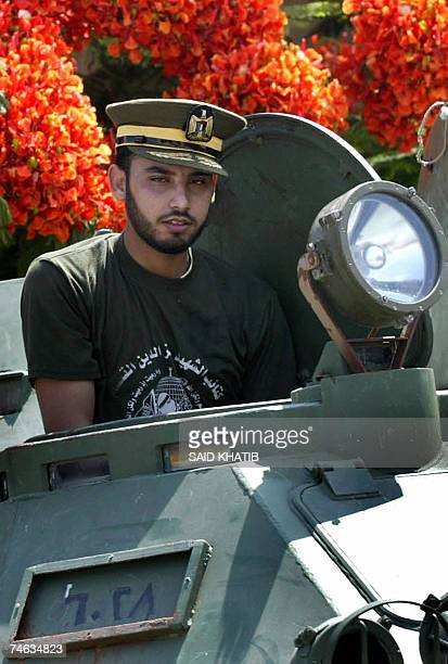 Hamas militant poses with a trophy a Fatahaffiliated Force 17 presidential guard cap as he secures the seafront presidential compound home to the...