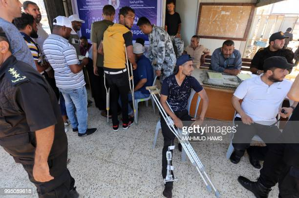 Hamas officials register the passport details of injured Palestinians preparing to board a blockaderunning boat carrying them with other students out...