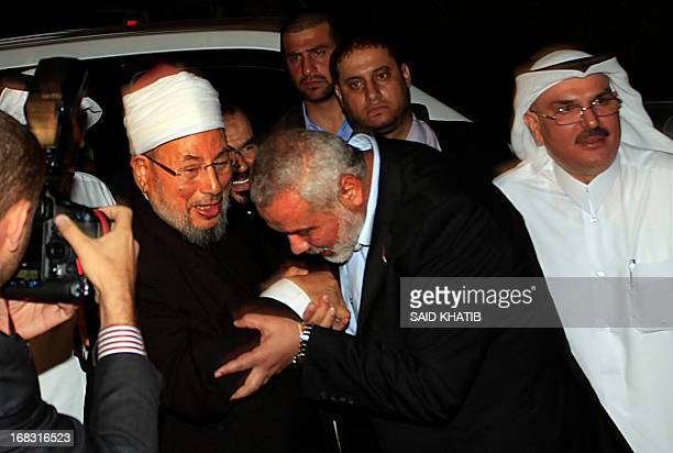 Hamas Prime Minister Ismail Haniyeh kisses the hand of Egyptian Cleric and chairman of the International Union of Muslim Scholars Sheikh Yusuf...