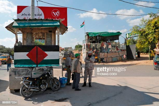 Hamas security men stand guard a at checkpoint sill held by the Islamist group near an area they handed over the control to the Palestinian Authority...