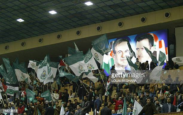 Hamas supporters wave party flags under portraits of late Syrian president Hafez alAssad and current President Bashar alAssad as they attend a...