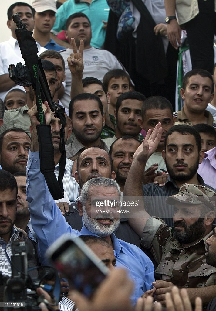 Hamas top leader in the Gaza Strip Ismail Haniya (C) brandishes a weapon during a rally in Gaza City on August 27, 2014, following a deal hailed by Israel and the Islamist movement as 'victory' in the 50-day war. The agreement, effective from 1600 GMT on August 26, saw the warring sides agree to a 'permanent' ceasefire which Israel said would not be limited by time, in a move hailed by Washington, the United Nations and top world diplomats.