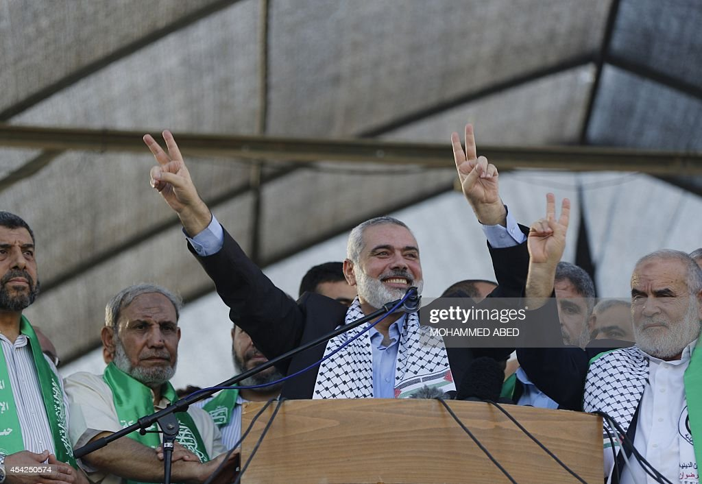 Hamas top leader in the Gaza Strip Ismail Haniya (C), standing next to Senior Hamas leader Mahmud al-Zahar (2nd from L), flashes the V-sign for 'victory' during a rally in Gaza City on August 27, 2014, following a deal hailed by Israel and the Islamist movement as 'victory' in the 50-day war. The agreement, effective from 1600 GMT on August 26, saw the warring sides agree to a 'permanent' ceasefire which Israel said would not be limited by time, in a move hailed by Washington, the United Nations and top world diplomats.