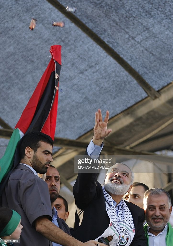 Hamas top leader in the Gaza Strip Ismail Haniya (C) throws sweets at the crowd during a rally in Gaza City on August 27, 2014, following a deal hailed by Israel and the Islamist movement as 'victory' in the 50-day war. The agreement, effective from 1600 GMT on August 26, saw the warring sides agree to a 'permanent' ceasefire which Israel said would not be limited by time, in a move hailed by Washington, the United Nations and top world diplomats.