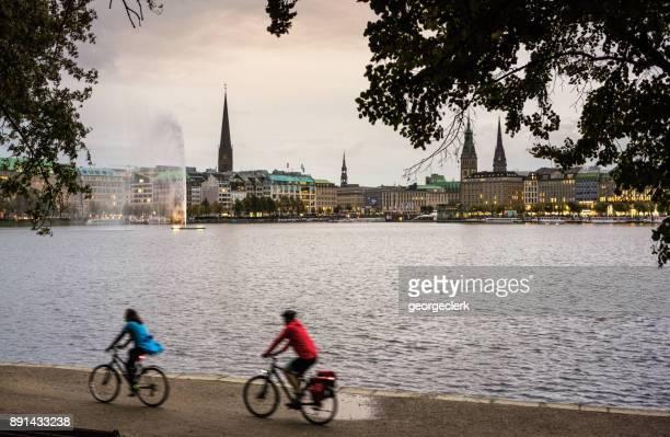 Hamburg - Radfahrer vorbei Binnenalster See in der Abenddämmerung