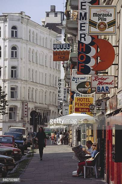 Hamburg: die Bremer Reihe in St. Georg. Auf der rechten Seite Schilder von Hotels und Bars. Auf dem Gehweg stehen Sonnenschirme und einige Leute...