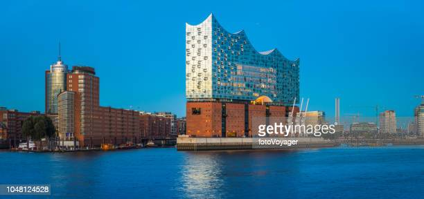 hamburg elbphilharmonie gleaming at dusk above river elbe panorama germany - elbphilharmonie stock pictures, royalty-free photos & images