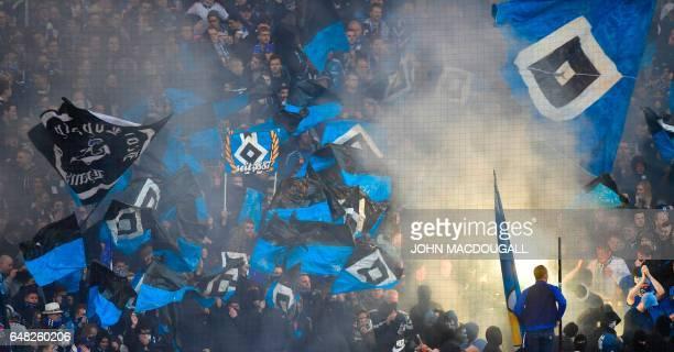Hamburg fans light flares during the German First division Bundesliga football match between Hamburg SV and Hertha Berlin on March 5 2017 / AFP PHOTO...