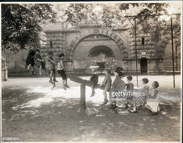 Photo shows children at playing on the seesaw at the zoological garden Undated