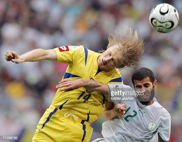 Ukrainian midfielder Andriy Gusin heads the ball with Saudi defender Abdulaziz Khathran during the World Cup 2006 group H football match Saudi Arabia...