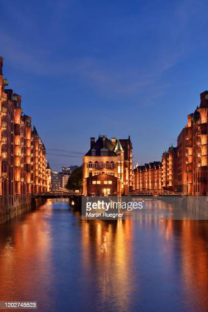 hamburg speicherstadt warehouses along the canal illuminated at night. in the middle is the famous wasserschloss. - unesco stock-fotos und bilder