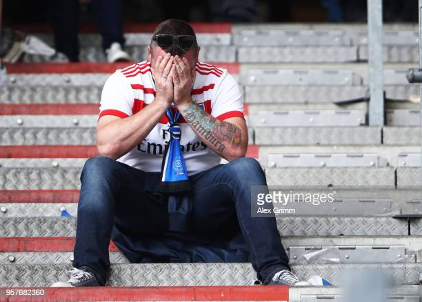 Hamburger SV fan looks dejected after the Bundesliga match between Hamburger SV and Borussia Moenchengladbach at Volksparkstadion on May 12 2018 in...