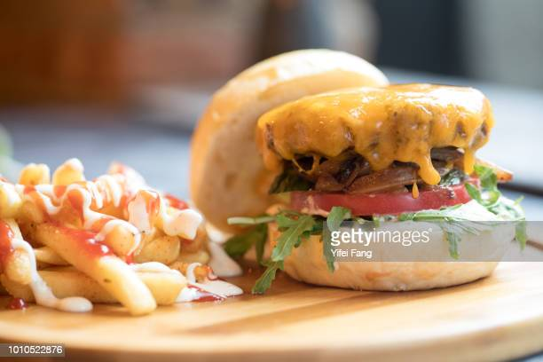 Hamburger with french fries served on wooden plate