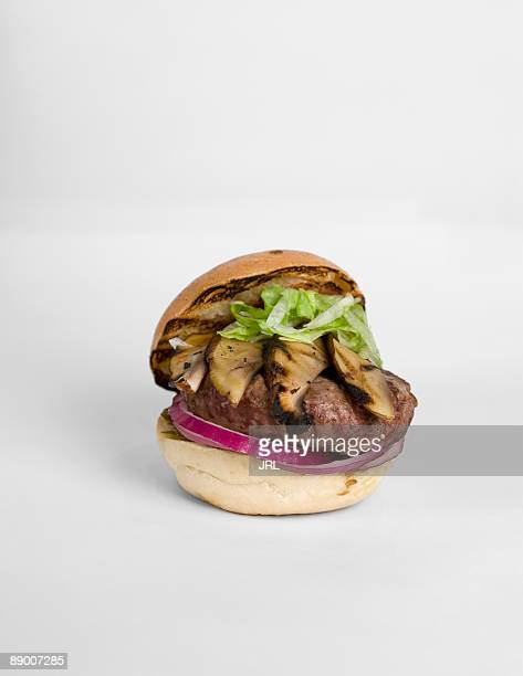 Hamburger with mushrooms , shredded lettuce , and red onions