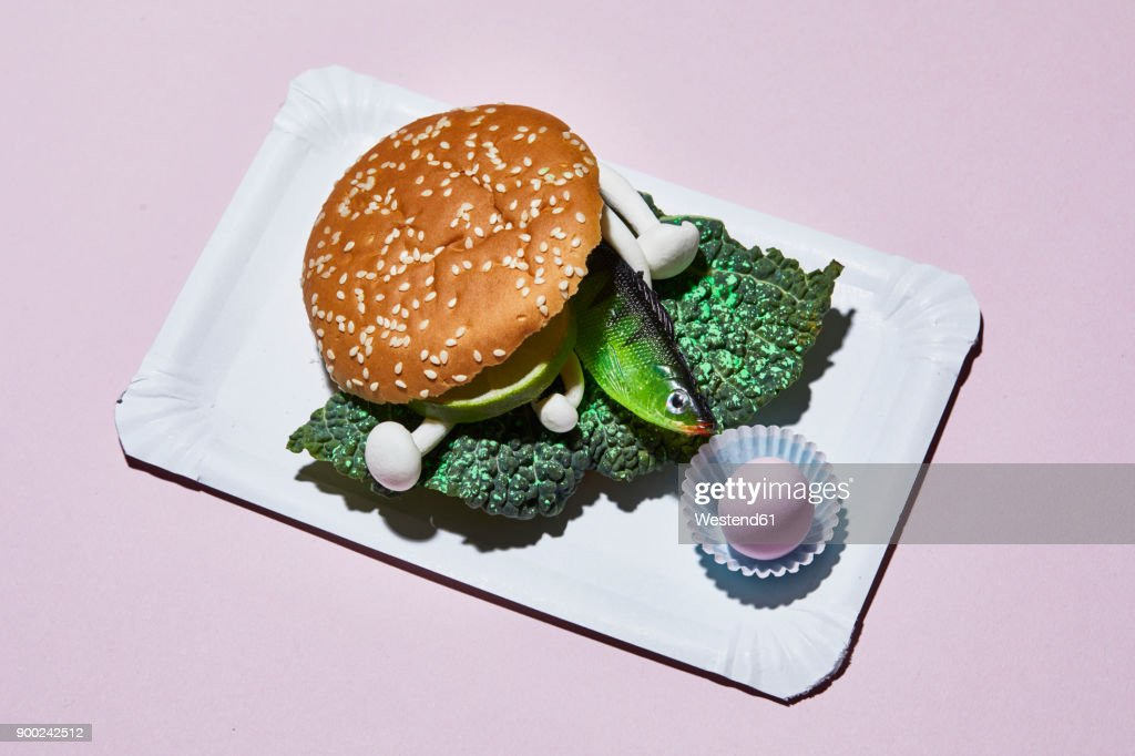Hamburger with toy fish on paper plate : Stock Photo