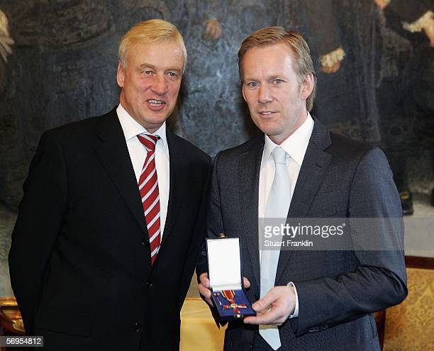 Hamburg's Burgermeister Ole Von Beust presents TV Presenter Johannes B Kerner with the Federal Cross of Merit at the town hall on February 28 2006 in...
