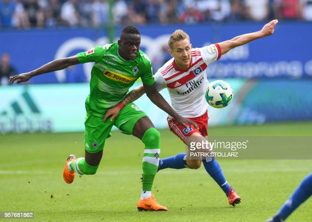 Hamburg's German midfielder Lewis Holtby and Moenchengladbach's French defender Mamadou Doucoure vie for the ball during the German first division...