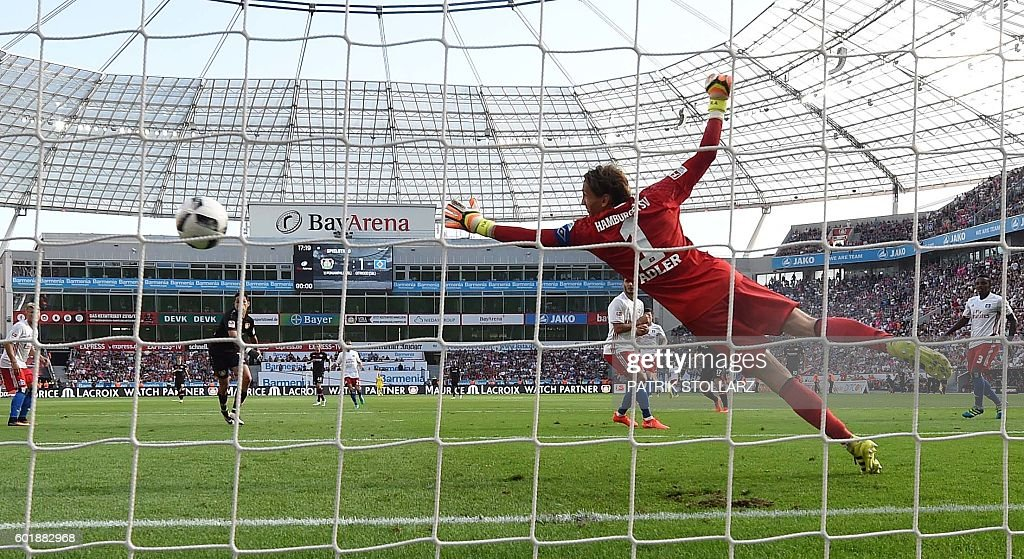 Hamburg's goalkeeper Rene Adler missies a goal from Leverkusen´s Joel Pohjanpalo during German first division Bundesliga football match between Bayer 04 Leverkusen and Hamburger SV in the Bay Arena in Leverkusen, western Germany on September 10, 2016. / AFP / PATRIK